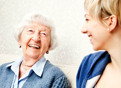 elderly woman and social worker laughing